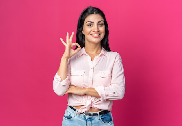 Young beautiful woman in casual clothes  happy and positive smiling cheerfully showing ok sign standing over pink wall