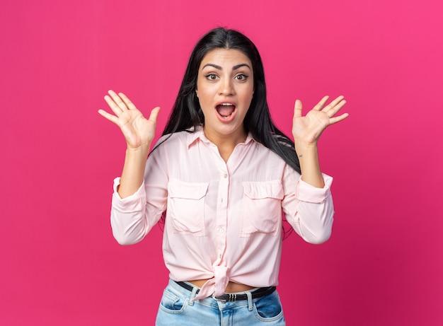 Giovane bella donna in abiti casual felice e sorpresa con le braccia alzate in piedi sul muro rosa