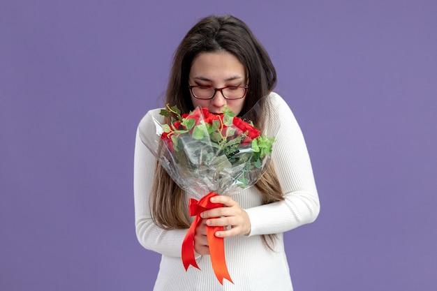 Giovane bella donna in abiti casual tenendo il mazzo di rose rosse felice e allegro sorridente concetto di san valentino in piedi sul muro viola