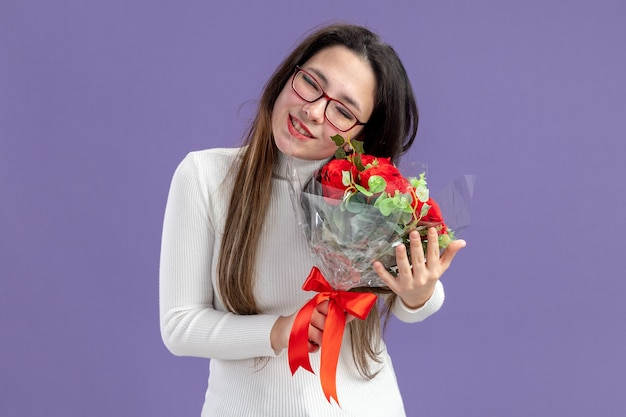 Young beautiful woman in casual clothes holding bouquet of red roses happy and positivesmiling feeling thankful valentines day concept standing over purple wall
