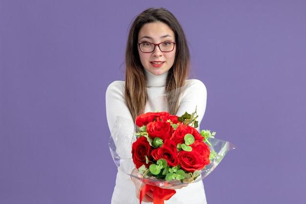 Giovane bella donna in abiti casual tenendo il mazzo di rose rosse guardando la telecamera felice e positivo sorridendo allegramente il giorno di san valentino concetto in piedi sul muro viola