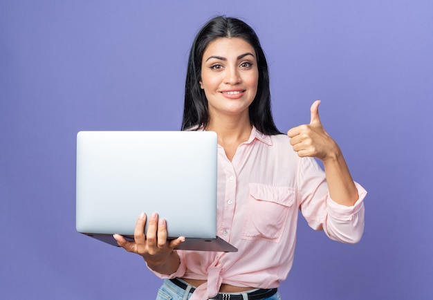 Young beautiful woman in casual clothes holding laptop happy and positive looking smiling confident showing thumb up