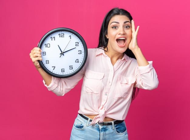 Giovane bella donna in abiti casual con orologio da parete che sembra felice e sorpresa
