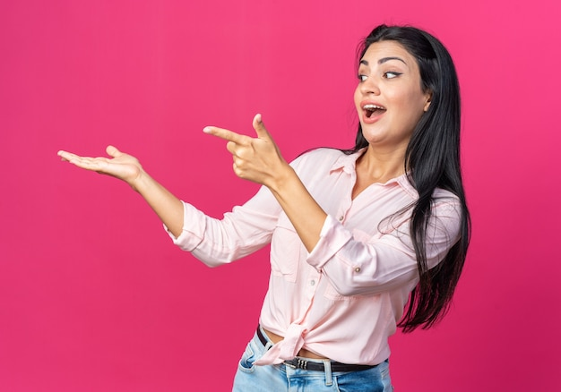 Giovane bella donna in abiti casual che guarda da parte felice ed eccitata che punta con il dito indice a qualcosa che si presenta con il braccio della mano in piedi sul rosa