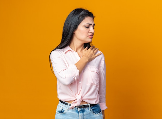 Young beautiful woman in casual clothes looking unwell touching her shoulder feeling pain standing on orange