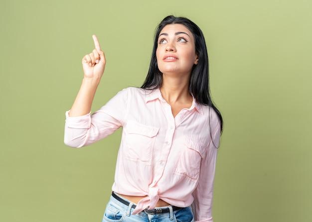 Giovane bella donna in abiti casual che guarda in alto indicando con il dito indice qualcosa che sorride in piedi sul muro verde