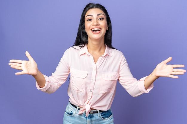Giovane bella donna in abiti casual che sorride ampiamente facendo un gesto di benvenuto che apre le mani in piedi sul muro blu