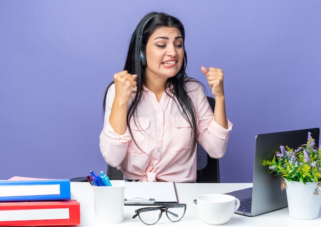 Giovane bella donna in abiti casual che indossa l'auricolare con il microfono che stringe i pugni arrabbiato e deluso seduto al tavolo con il computer portatile su blue