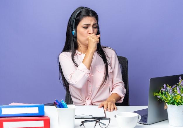 Giovane bella donna in abiti casual che indossa le cuffie con microfono che tossisce guardando male seduta al tavolo con il computer portatile su blue