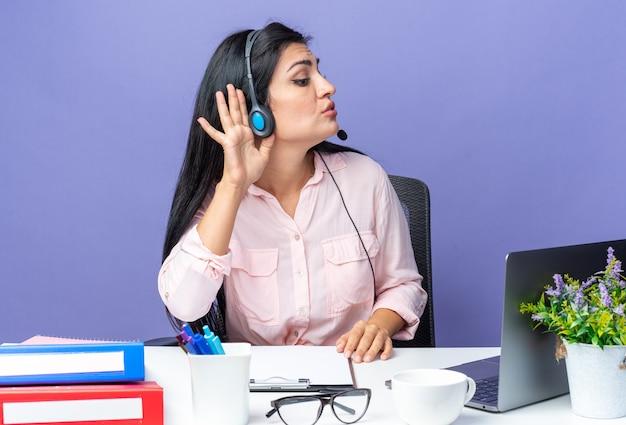 Giovane bella donna in abiti casual che indossa l'auricolare con microfono che tiene la mano sull'orecchio cercando di ascoltare seduto al tavolo con il computer portatile sul muro blu che lavora in ufficio