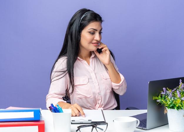 Giovane bella donna in abiti casual che indossa l'auricolare con microfono che sembra sicura di sé sorridente seduta al tavolo con il computer portatile su sfondo blu che lavora in ufficio