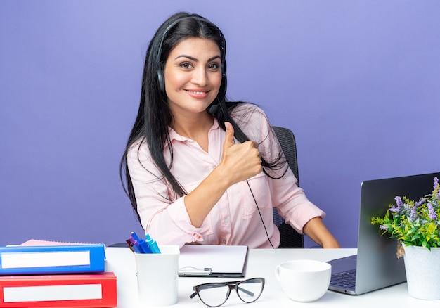 Giovane bella donna in abiti casual che indossa l'auricolare con microfono che sembra sorridente fiducioso che mostra i pollici in su seduto al tavolo con il computer portatile su sfondo blu che lavora in ufficio