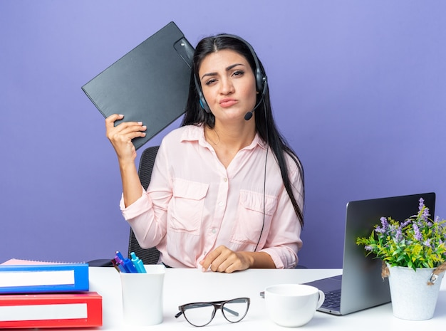 Young beautiful woman in casual clothes with headphones and microphone holding clipborad looking confused and displeased sitting at the table with laptop over blue wall working in office