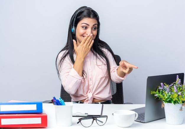 Giovane bella donna in abiti casual con cuffie e microfono seduto al tavolo con il computer portatile puntato con il dito indice sullo schermo sorridendo allegramente su sfondo bianco lavorando in ufficio