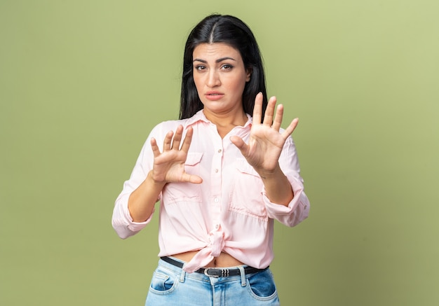 Young beautiful woman in casual clothes  worried making defense gesture with hands standing over green wall