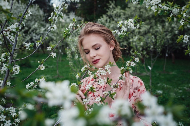 Young beautiful woman in the cherry-blossoming garden.