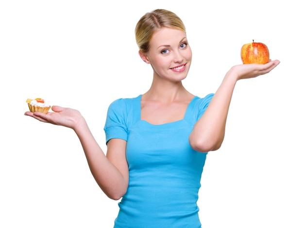 若い美しい女性は甘いケーキと赤いリンゴから選択します
