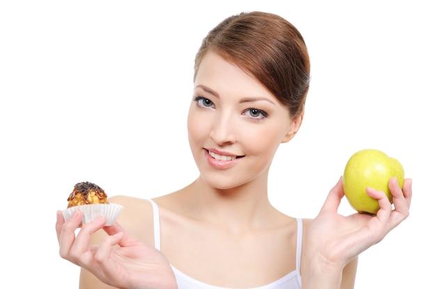 Молодая красивая женщина, выбирая между сладостями и здоровой пищей
