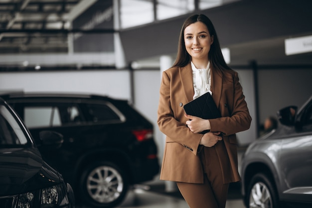 Young beautiful woman choosing car in a car showroom