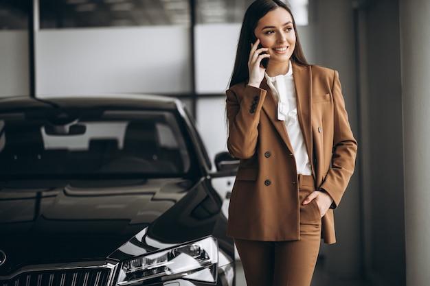 Young beautiful woman choosing car in a car showroom