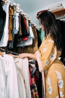 自宅で彼女のワードローブの服を選ぶ若い美しい女性