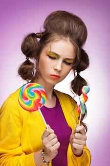 먹을 어떤 다채로운 막대 사탕을 선택하는 젊은 아름 다운 여자