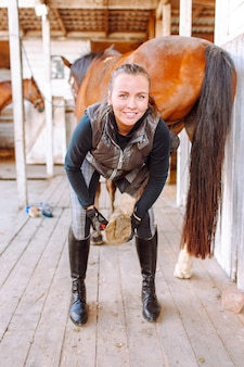 Young beautiful woman cleans the horse's hooves with a special brush before riding
