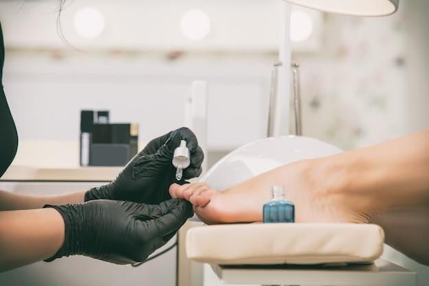 Молодая красивая женщина-клиент делает педикюр от профессионального мастера в салоне красоты крупным планом стопы