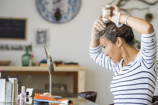 化学製品で自宅で自分の髪を着色する若い美しい女性-大人の女性の白人の人々のための白髪と白髪の老化治療-美容ケアのない活動