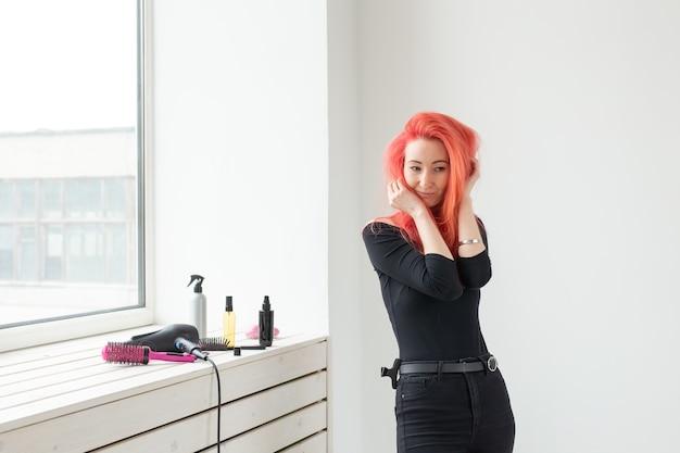 リビングルームで髪をとかす若い美しい女性。