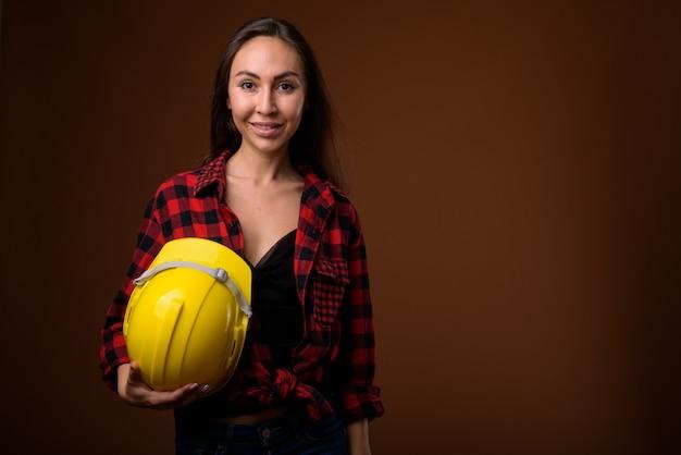 茶色の背景の若い美しい女性建設労働者