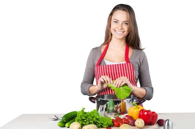 Young beautiful woman cooking on white background