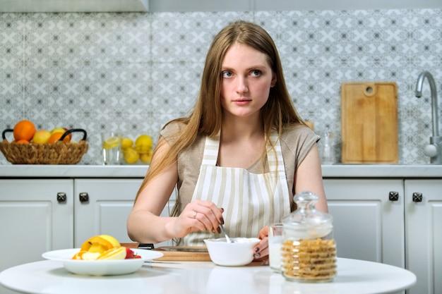 若い美しい女性は家でおいしい健康的なダイエット食品を調理します。テーブルの上には果物、シリアル、乳製品があります。美しさ、若さ、健康的なライフスタイルと健康的な食事