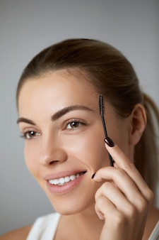 Young beautiful woman correcting shape of eyebrows on grey background, closeup.