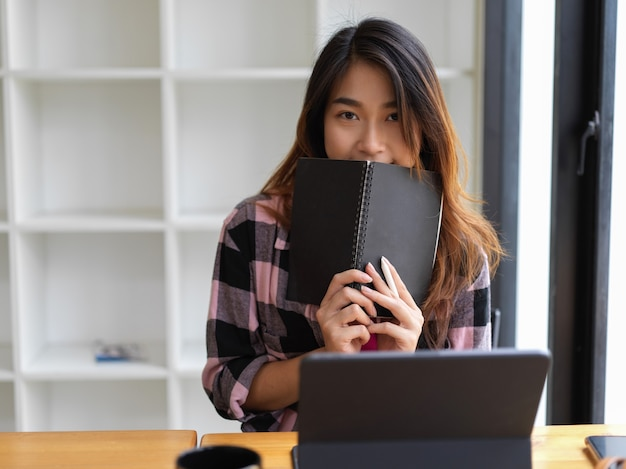 Young beautiful woman cover her mouth with notebook in modern workspace