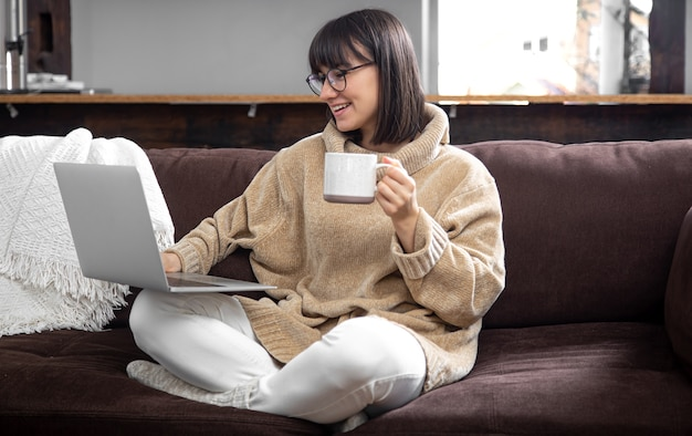 Young beautiful woman in a cozy sweater with a mug of drink works at a laptop. remote work at home and freelancing.