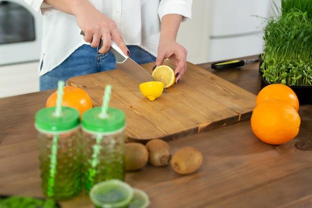 若い美しい女性は、マイクログリーンとフルーツで作られたビタミンスムージーのためにテーブルのキッチンでレモンをカットします。
