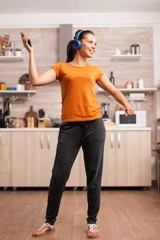 キッチンで青いワイヤーレスヘッドフォンで音楽を聴きながら踊る若い美しい女性