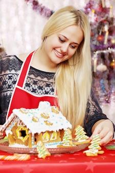 아름 다운 젊은 여자 장식 진저 브레드 하우스