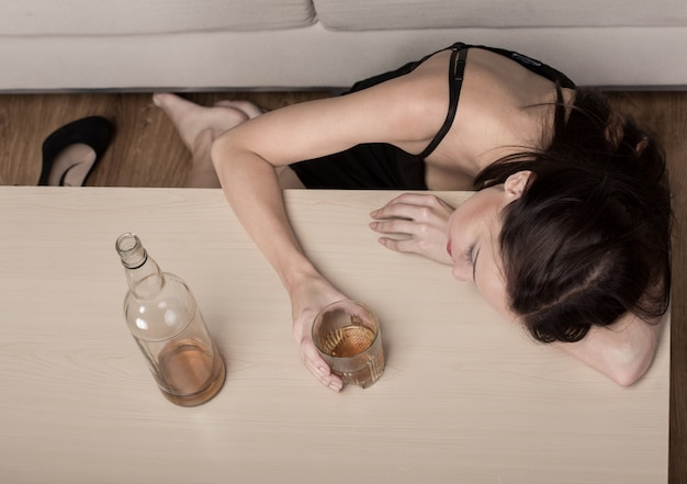 Young beautiful woman in depression, is drinking alcohol.