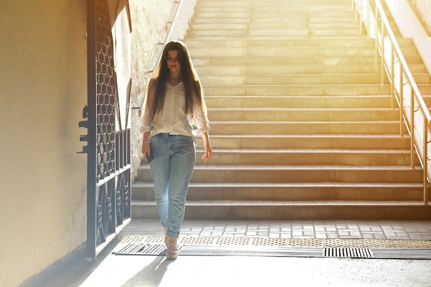 Young beautiful woman descended the steps to the underpassand