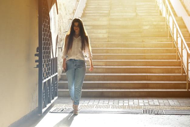 젊은 아름 다운 여자는 지하도 계단을 내려