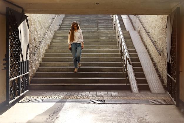 Молодая красивая женщина спускается по ступеням в пешеходный переход