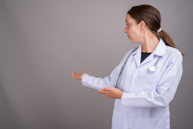 灰色の背景の若い美しい女性医師