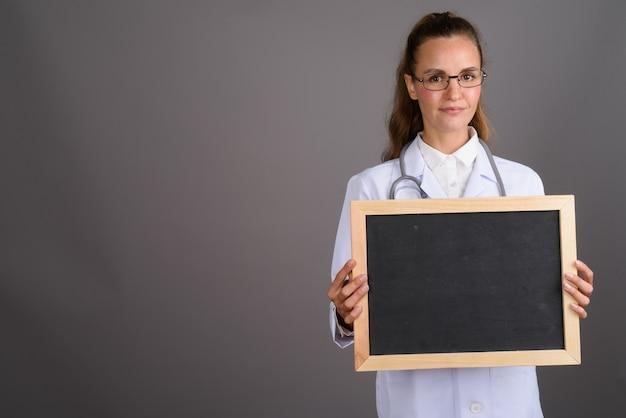 Молодая красивая женщина-врач на сером фоне