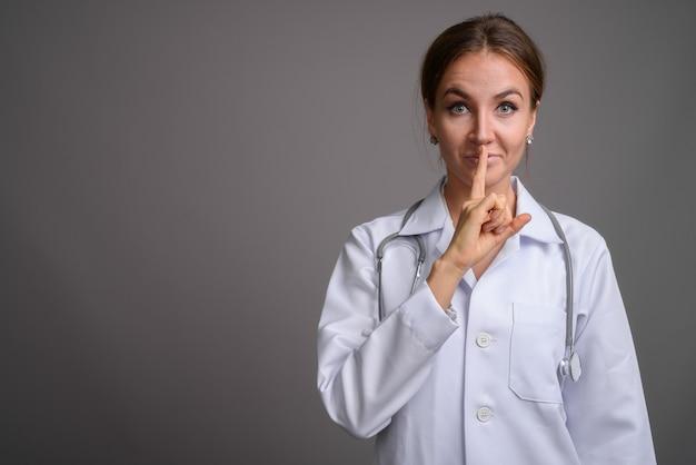 灰色の壁に対して若い美しい女性医師