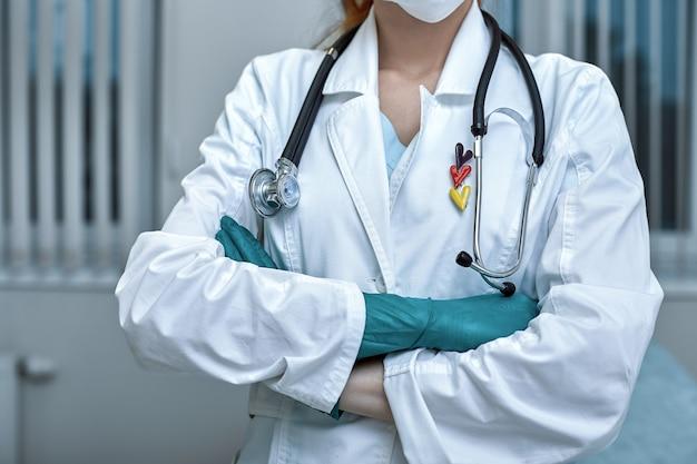 Молодая красивая женщина-врач в белой форме и маске на лице со стетоскопом крупным планом