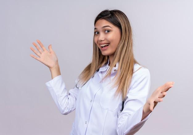 聴診器で白衣を着た若い美しい女性医師は、歓迎のジェスチャーを作る幸せで前向きな笑顔の広い開口部の手