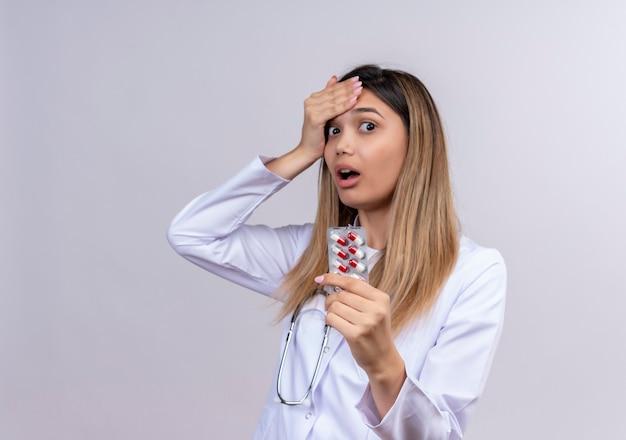 Giovane bella donna medico indossa camice bianco con lo stetoscopio che tiene la bolla con le pillole che sembra stupito e sorpreso