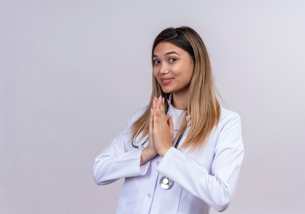 Young beautiful woman doctor wearing white coat with stethoscope holding hand in prayer namaste gesture feeling thankful and happy